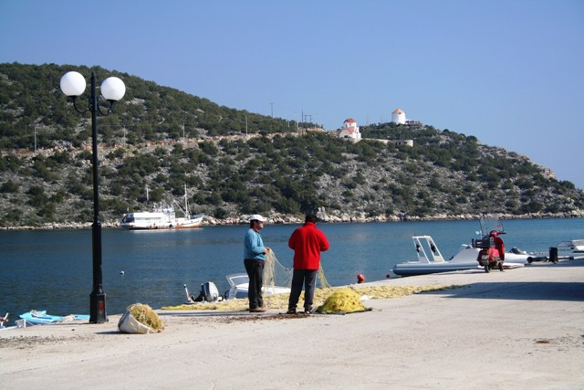 Fishermen mending their nets at Limani